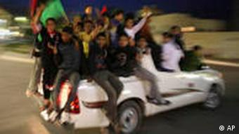 Libyan boys flash victory signs as they wave Libyan pre-Gadhafi flags while riding a pickup truck in Benghazi, Libya, Wednesday, March 30, 2011. Rebels retreated Wednesday from the key Libyan oil port of Ras Lanouf along the coastal road leading to the capital Tripoli after they came under heavy shelling from ground forces loyal to leader Moammar Gadhafi. In a dramatic move Libya's Foreign Minister Moussa Koussa arrived in the UK late Wednesday and is resigning from his post, according to Britain's Foreign Office. (Foto:Altaf Qadri/AP/dapd)