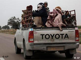 Libyans ride with their belongings at the back of a pickup truck at the main road heading to Benghazi, while fleeing the eastern town of Ajdabiya, Libya Wednesday, March 30, 2011. Moammar Gadhafi's ground forces recaptured a strategic oil town Wednesday and were close to taking a second, making new inroads in beating back a rebel advance toward the capital Tripoli. (AP Photo/Nasser Nasser)