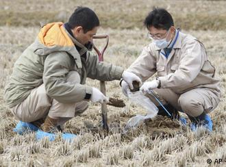 Fukushima Prefectural officers collect soil to check if it is contaminated by radioactive materials or not at a rice paddy in Kunimimachi, northern Japan Thursday, March 31, 2011. (AP Photo/Yomiuri Shimbun, Tsuyoshi Yoshioka) JAPAN OUT, MANDATORY CREDIT
