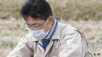 Fukushima Prefectural officers collect soil to check if it is contaminated by radioactive materials or not at a rice paddy in Kunimimachi, northern Japan Thursday, March 31, 2011. (AP Photo/Yomiuri Shimbun, Tsuyoshi Yoshioka)