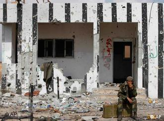 A Libyan rebel fighter sits near to the western gate of Ajdabiya, Libya, Friday, April 1, 2011