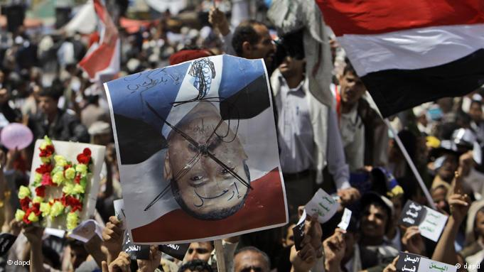 An anti-government protestor holds up a defaced poster of Yemeni President Ali Abdullah Saleh that reads in Arabic Leave, during a demonstration demanding the resignation of Yemeni President Ali Abdullah Saleh, in Sanaa,Yemen, Friday, April 1, 2011. Hundreds of thousands of Yemenis have packed a main square in the capital and are on the march elsewhere across the nation, demanding the country's ruler of 32 years step down. (Foto:Muhammed Muheisen/AP/dapd)