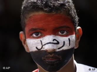 An anti-government protestor, his face painted with the colours of his national flag looks on during a demonstration demanding the resignation of Yemeni President Ali Abdullah Saleh, in Sanaa,Yemen, Friday, April 1, 2011. Hundreds of thousands of Yemenis have packed a main square in the capital and are on the march elsewhere across the nation, demanding the country's ruler of 32 years step down. Arabic reads on his face, Leave. (AP Photo/Muhammed Muheisen)