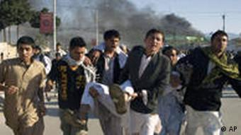 Afghans carrying a man, who got wounded following an attack on UN's office during a demonstration to condemn the burning of a copy of the Muslim holy book by a Florida pastor, in Mazar-i- Sharif north of Kabul, Afghanistan on Friday, April. 1, 2011. An Afghan official says seven people have been killed at a U.N. office in the northern city of Mazar-i-Sharif when a Quran burning protest turned violent. (AP Photo/Mustafa Najafizada)