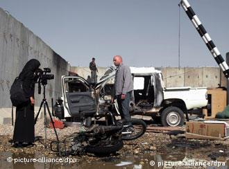 An Afghan journalist films the compound of UN office which was attacked by demonstrators,