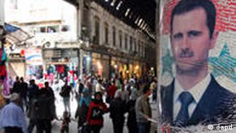 A poster of Assad at a market in Damascus