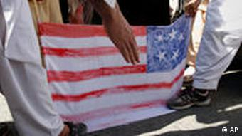 Afghan protestors step on a hand-made U.S. flag during a demonstration in Jalalabad, Afghanistan on Sunday, April 3, 2011. Afghan protests against the burning of a Quran in Florida entered a third day with a demonstration in the major eastern city Sunday, while the Taliban called on people to rise up, blaming government forces for any violence. (AP Photo/Rahmat Gul)