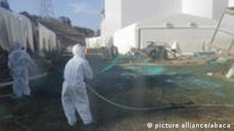 File photo taken April 1, 2011. Workers wearing protective suits spray adhesive synthetic resin over the ground at the Tokyo Electric Power Co. (TEPCO)'s Fukushima Daiichi Nuclear Power Plant in Fukushima prefecture, Japan. The drama at the six-reactor Fukushima Daiichi complex has dragged into a fourth week, unsettling the global nuclear industry and compounding Japan's suffering after an earthquake and tsunami that left about 27,500 people dead or missing. Radiation has leaked into the sea, food, drinking water and air. It is hindering efforts to cool overheating fuel rods work at the plant and regain control of the damaged reactors. Photo via ABACAPRESS.COM