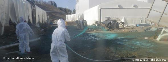 Men in white spray water on an area of the Fukushima plant