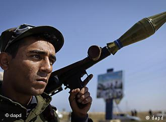A rebel fighter holds a rocket propelled grenade launcher