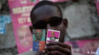 A supporter of Haiti's presidential candidate Michel 'Sweet Micky' Martelly shows Martelly's picture, right, next to a picture of Haiti's former President Jean-Bertrand Aristide before the announcement of preliminary election results in Port-au-Prince, Haiti, Monday April 4, 2011. According to electoral officials, preliminary results show Martelly won the presidential election runoff, defeating former first lady Mirlande Manigat. Aristide returned to Haiti in March after seven years of exile in South Africa. (Foto:Ramon Espinosa/AP/dapd)