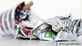Umgestürzter Papierkorb mit Zeitungen