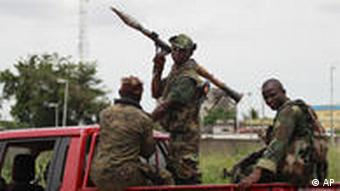 Soldiers loyal to Alassane Ouattara arrive at a checkpoint at one of the principal entrances to Abidjan