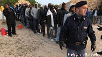 Line of migrants and a police officer