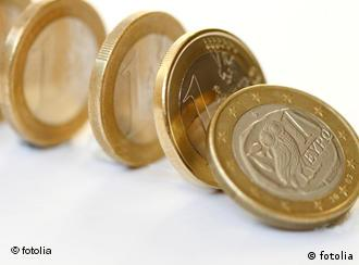 Euro coins standing on end, tipping toward each other