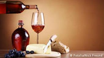 Red wine being poured into a glass with French cheese and bread on a table