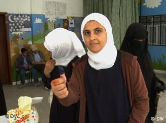 A girl holding up her ink-covered thumb after voting