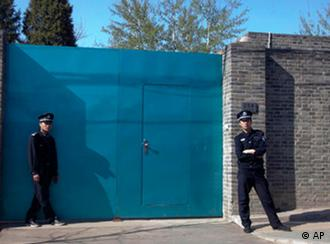 A Chinese police officer, right, and a security guard stand outside the entrance to Ai Weiwei's studio in Beijing Sunday, April 3, 2011. China blocked Ai Weiwei, one of its most famous contemporary artists, from taking a flight to Hong Kong on Sunday and police later raided his Beijing studio, the man's assistant said. (AP Photo/Ng Han Guan)