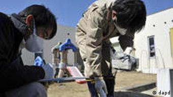 Prefectural government's employees monitor amount of radiation on the ground of a day-care center in Iitate, Fukushima