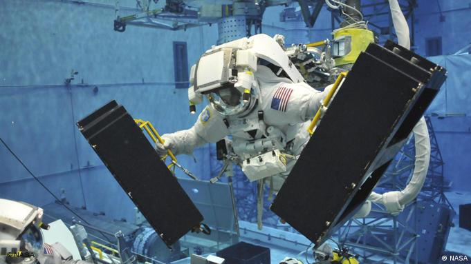 SM4 EVA astronaut Andrew Feustel practices installing new battery modules on the Hubble Space Telescope. In this photograph, taken underwater at the Neutral Buoyancy laboratory at the Johnson Space Center in Houston, Texas, Andrew is shown handing an old battery module to EVA astronaut John Grunsfeld while preparing to take a new battery module to the telescope. Astronauts spend many hours choreographing their procedures in order to be as efficient as possible while performing spacewalks to repair and upgrade the telescope. Credit:NASA