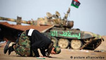 epa02672083 A Libyan rebel fighter prays near the front line on the road between Ajdabiya and Brega, Libya, on 06 April 2011. According to media sources, the military leader of the Libyan rebels, General Abdul Fattah Younis, confirmed on 06 April in a television interview that his forces had received weapons from allied countries. He had earlier criticized NATO for not being quick enough with airstrikes against Libyan Leader Muammar Gaddafi's forces. EPA/VASSIL DONEV