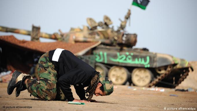 Libyen rebel conducts daily prayer in front of tank