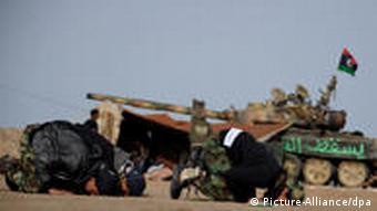 Libysche Rebellen beten an der Frontlinie in Brega (Foto: EPA)