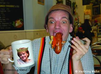 hennign Wehn eating a sausage and holding a mug with Angela Merkel on it