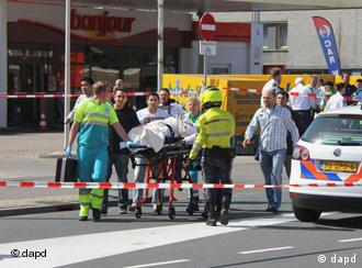 Injured people are carried out of a shopping mall