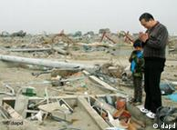 Мужчина с ребенком оплакивает жертв цунами в Японии