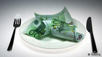 Money is shown on a plate next to a knife and fork