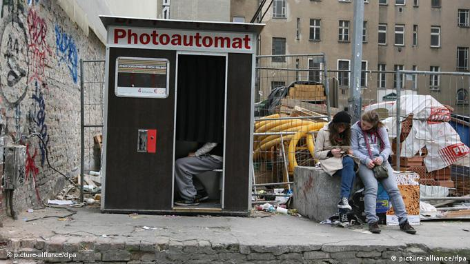 A man sits in a photo-booth located on Warschauer Strasse in Berlin