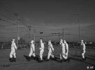 In this Thursday April 7, 2011 photo, Japanese police wearing protective radiation suits search for the bodies of victims of the tsunami in the Odaka area of Minamisoma, inside the deserted evacuation zone established for the 20 kilometer radius around the Fukushima Dai-ichi nuclear reactors. (AP Photo/David Guttenfelder)