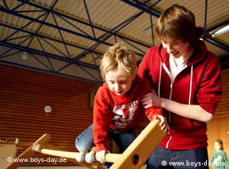 A young man helps a boy onto some climbing equipment