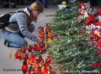 Девушка возлагает цветы у входа на станцию метро Октябрьская
