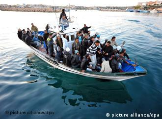 Overloaded boat carrying North African migrants landing in Italy