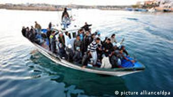 epa02684433 A boat of migrants arriving on the island of Lampedusa, southern Italy on 12 April 2011. Reports state that Italian Foreign Minister Franco Frattini on 12 April 2011 downplayed comments made the day before by Interior Minister Roberto Maroni about Italy leaving the European Union. Maroni had only been expressing 'his strong disappointment' amid a row over migration, Frattini said. Maroni on 11 April 2011 failed to secure any support from his EU counterparts for Italy_s decision to issue temporary visas to thousands of North African migrants who have landed on its shores, allowing them to travel within the border-free Schengen area. EPA/ETTORE FERRARI +++(c) dpa - Bildfunk+++