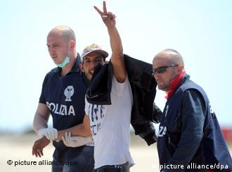 epa02684249 One of the 30 Tunisian migrants kept in a Lampedusa reception center gestures while policemen escort him before his repatriation on 12 April 2011 at the airport on the Italian island of Lampedusa, on 12 April 2011. Since Tunisia's authoritarian president Zine el-Abidine Ben Ali was toppled by a popular uprising in January, some 23,000 Tunisians have arrived in Italy, mostly to the overburdened island of Lampedusa. EPA/ETTORE FERRARI +++(c) dpa - Bildfunk+++