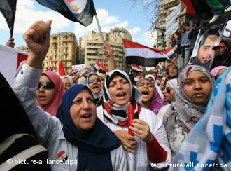 Women wave flags at a demonstration in Cairo