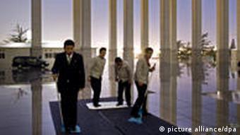 Mitarbeiter des National Museum of China trocknen am Freitag (01.04.2011) während des Festaktes anlässlich der Eröffnung der Ausstellung Die Kunst der Aufklärung aufgrund des Regens einen Teppich am Eingang des Museums mit Aufnehmern und Handtüchern. Bundesaußenminister Westerwelle (FDP) eröffnete die Ausstellung, die von den Staatlichen Museen in Berlin, München und Dresden vorbereitet wurde. Das Museum gilt als das derzeit größte Museum der Welt.Foto: Arno Burgi dpa
