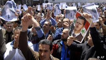 Syrian pro-government protesters carry pictures of Syrian President Bashar Assad as they shout slogans after Friday prayers outside the Omayyad Mosque in Damascus, Syria, Friday, April 15, 2011. (AP Photo/Muzaffar Salman)