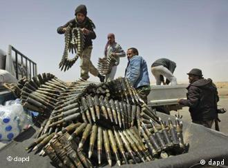 Rebels load a truck with ammunition on the outskirts of Ajdabiya