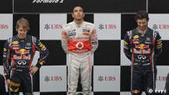 McLaren Formula One driver Lewis Hamilton, centre, of Britain looks skywards as his national anthem is played after his win in the Chinese Formula One Grand Prix at the Shanghai International Circuit in Shanghai, China, Sunday, April 17, 2011. Red Bull Formula One driver Sebastian Vettel of Germany was second and his teammate Mark Webber, right, of Australia was third. (Foto:Mark Baker/AP/dapd)