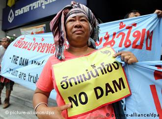 Thai villagers hold banners reading 'Love Mekong, No Dam' to protest against the proposed dam 'Xayaburi'