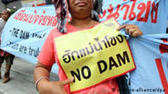 Thai villagers hold banners reading 'Love Mekong, No Dam' during a demonstration