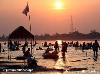 Tourists enjoy the low running Mekong River at sunset on the border of the two Southeast Asian nations