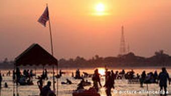 (FILE) A file photograph shows Thai and Laos tourists enjoying the low running Mekong river at sunset on the border of the two south east Asian nations, at the northern Thai border town of Nong Khai, Thailand, 29 March 2009.