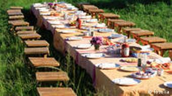 Ein langer, gedeckter Tisch im Freien mit Sitzhockern