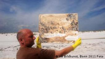 Ruppe Koselleck holds up a crude oil painting at the beach