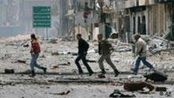 A rebel picks his way through a ruined street in Misrata, Libya